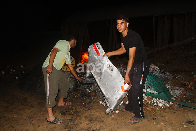 Palestinians check the damage to a car after an Israeli attack in Deir al-Balah in the central Gaza Strip on September 7, 2011. The hardline Islamic Jihad group said that the dead man, Remah al-Hasani, was a member of its military wing, the Al-Quds Brigades. He was killed as he was driving in the central Deir al-Balah district of the territory, medics said . Photo by Ashraf Amra