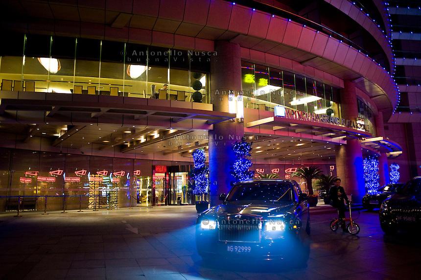 Una Rolls Royce esce da un elegante albergo.<br /> A Rolls Royce leave a luxurious hotel
