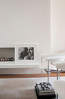 A photograph of Ben de Lisi and his partner Gerardo Vidaurre is propped against the minimal fireplace