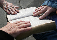 Church members place thier hands on a Bible pulled from the debris in the sanctuary of the Mountain Creek Baptist Church Tuesday morning.