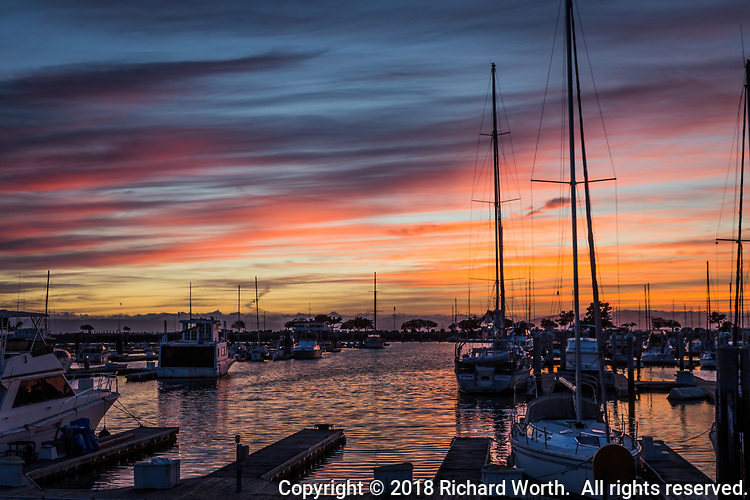 A sky streaked with sunset orange, blue and gray over sailboats moored at the San Leandro Marina along San Francisco Bay.