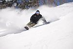 Male snowboarder making snowy turns down Outer Limits, a double black diamond trail, Killington, Vermont.