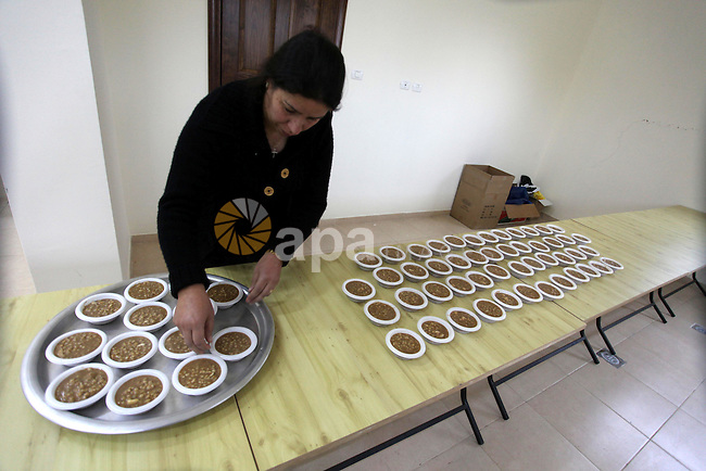 A Palestinian woman makes traditional sweets to mark the annual festival of St. Barbara's Day in the Palestinian village of Abud, in the Israeli occupied West Bank on December 16, 2012. Photo by Issam Rimawi