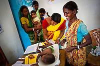 A child is being weighed by clinic workers in a Nutrition Rehabilitation Centre in the Purulia district of the Eastern Indian state of West Bengal on the 29th of March 2011.