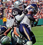 Oakland Raiders vs. San Diego Chargers at Oakland Alameda County Coliseum Sunday, October 11, 1998.  Raiders beat Chargers  7-6.  Oakland Raiders defensive back Eric Turner (42) tackles San Diego Chargers running back Natrone Means (20).