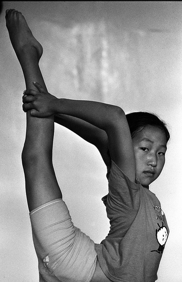 A Mongolian girl at her daily lesson in contortion at the Mongolian State Circus in Ulan Bator. Flexible children begin attending lessons at about five or six years of age, and hope to one day perform in the circus, earn a good income and travel around the world.