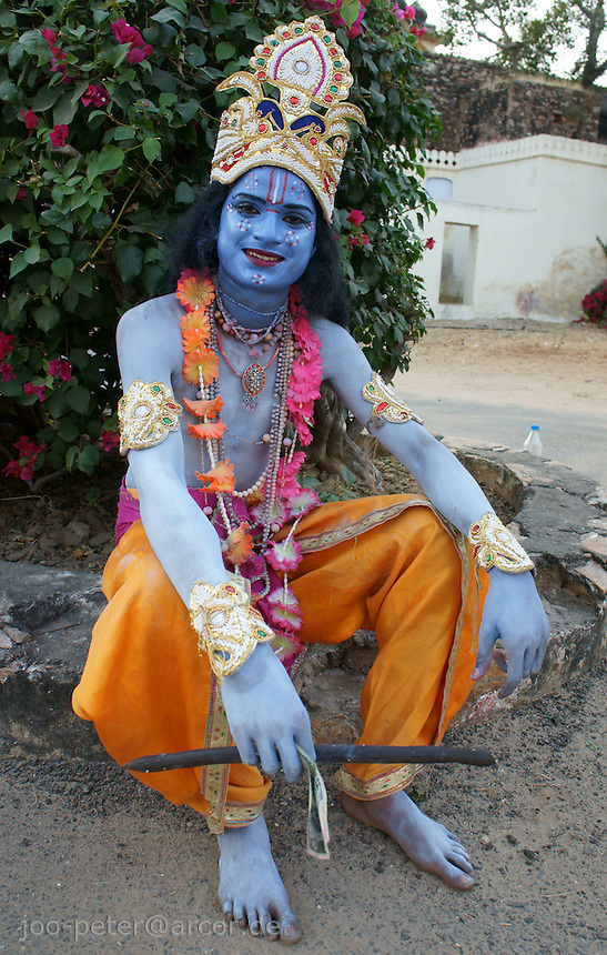 actor performing as krishna in street procession takes a rest  in Pushkar, Rajastan, India