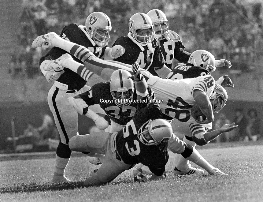 Raiders vs. 49ers: 49er Phil Frances is mobbed by host of Raidedrs, John Matuszak, Lester Hayes, Charles Phillips, Rod Martin, Monte Johnson, and Mike Davis..(1979 photo/Ron Riesterer)