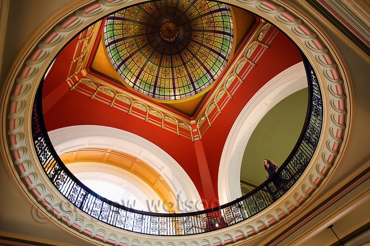 A woman looks up to the colourful stained-glass dome of the Queen Victoria Building - Sydney's oldest shopping complex.  Sydney, New South Wales, AUSTRALIA.