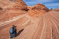 A photographer shoots the unusual sandstone rock formations at Coyote Buttes North, Arizona