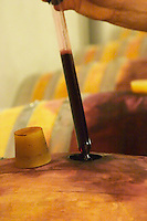 Cave P et Andre Perret in Chavanay, making Condrieu, Saint Joseph, Cote Rotie.  In the winery. Andre Perret taking a barrel sample of red wine with a pipette.  Andre André P et A Perret, Chavanay, Rhone, France, Europe