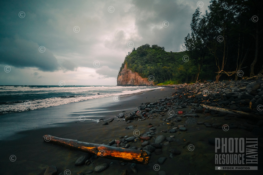 A hiker's view of Pololu Beach with waves and rocks on the North Kohala coastline of the Big Island.
