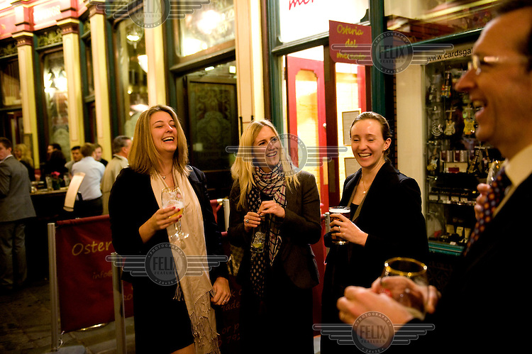 Three women drinking outside a pub in Leadenhall Market, in the City of London.