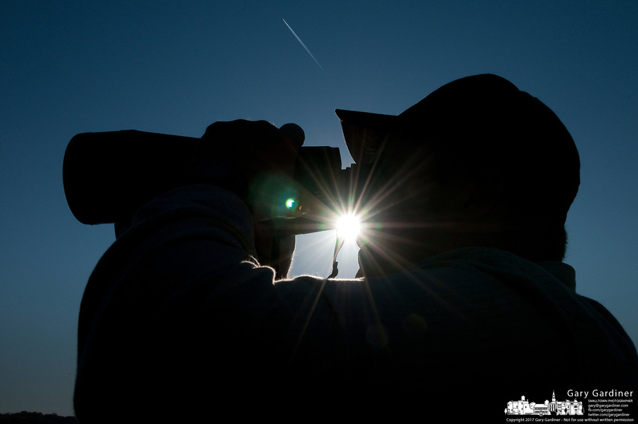 A parent of a high school rower watches competition through binoculars during early morning competition at the Fall Classic. The annual rowing competition is sponsored by the Westerville Rowing Club.