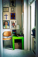 A detail of a corner of a room where a wood and metal Eames chair stands next to a green side table. A collection of artworks is displayed on the walls.