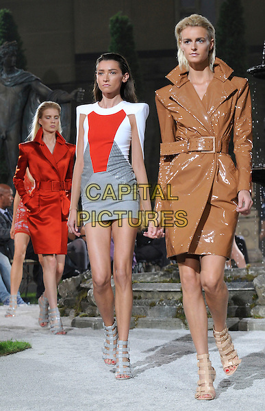 JACQUETTA WHEELER & MODELS .At the Julien MacDonald Show, London Fashion Week Day 3, The Lawrence Hall. Greycoat St. London, England, UK,.September 20th 2009..full length modeling catwalk runway brown shiny pvc trench coat mac red white and grey gray dress shoulder pads sandals .CAP/CAN.©Can Nguyen/Capital Pictures.