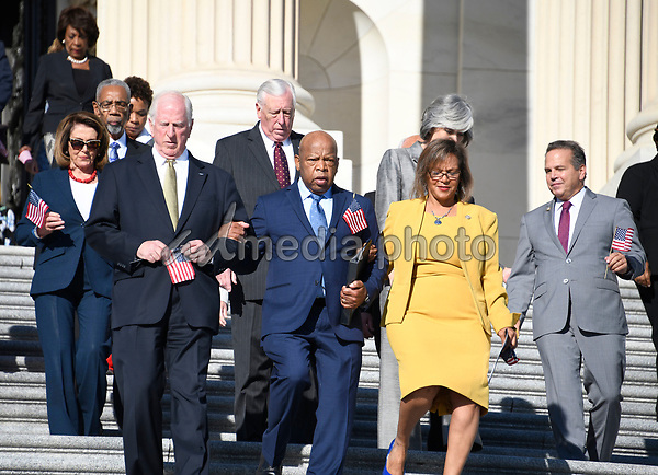 United States Representative John Lewis (Democrat of Georgia), center, and US Representative Mike Thompson (Democrat of California), left, and US Representative Robin Kelly (Democrat of Illinois) lead US House Democrats down the East Steps of the US Capitol to make a statement against gun violence in the wake of the Las Vegas Massacre in Washington, DC on Wednesday, October 4, 2017.  Also visible in the photo are US House Minority Leader Nancy Pelosi (Democrat of California), far left, and US House Minority Whip Steny Hoyer (Democrat of Maryland), slightly left behind Rep. Lewis.<br /> Photo Credit: Ron Sachs/CNP/AdMedia