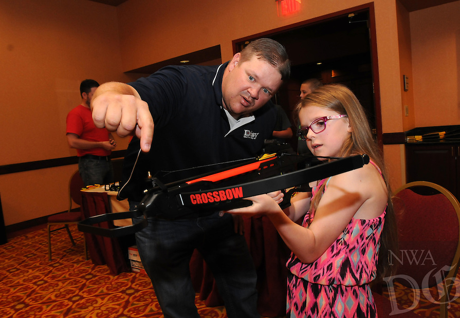 NWA Democrat-Gazette/FLIP PUTTHOFF<br /> ARROWS AND AIR GUNS<br /> Kyle Werst with Daisy air guns of Rogers shows Sophia Sudenga of South Dakota how to shoot a Daisy youth crossbow Wednesday July 1 2015 at the John Q. Hammons Center in Rogers. A youth archery range is part of the festivities at the 50th annual Daisy National BB Gun Championships set for Saturday and Sunday at the Hammons center. About 700 youth air gun shooters and their families on 68 teams from around the nation began arriving in Rogers Wednesday, said Ray Hobbs, president and CEO of Daisy. Practice rounds are today. The opening ceremony is from 6 to 8 p.m., Friday at the Hammons center, where the competition will be held. Each youngster gets to build their own Red Ryder BB gun from scratch with help from a Daily employee.