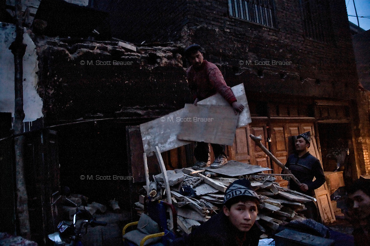 Uighur bakers collect scrap wood to use in their ovens in the Old Town section of Kasghar, Xinjiang, China.