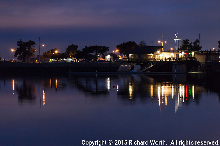 Twilight, and lights from the Spinnaker Yacht Club and the marina parking lot glitter and reflect in the waters at San Leandro Marina on San Francisco Bay.