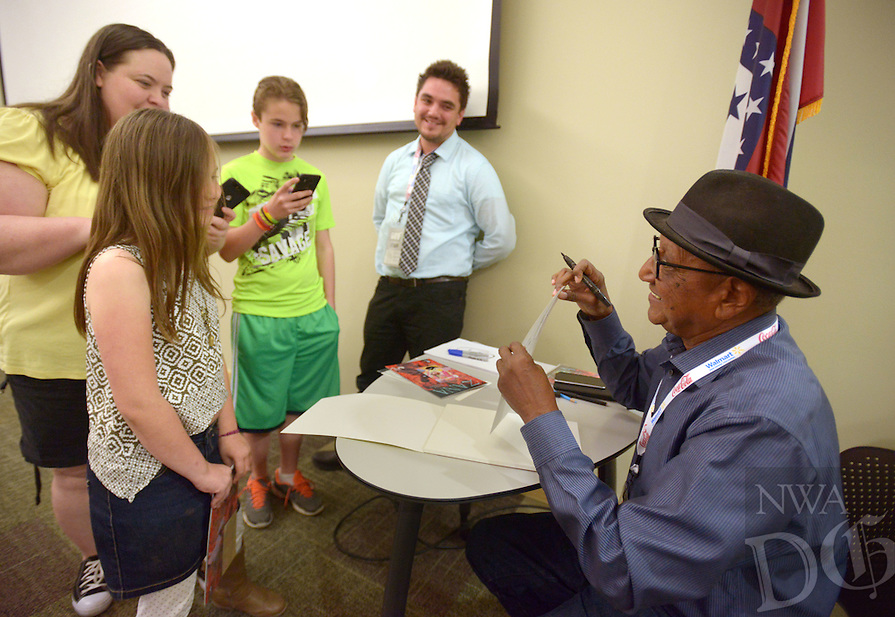 NWA Democrat-Gazette/BEN GOFF @NWABENGOFF<br /> Floyd Norman (right) sketches Donald Duck for Savannah Shoemaker, 10, as her mother Kristi Leverington and brother Kaiden Jackson, 12, of Centerton, watch on Saturday May 7, 2016 after the Bentonville Public Library's Free Comic Book Day panel in conjunction with the Bentonville Film Festival. In 1956, Norman became the first African-American animator at Disney and went on to build a long resume of work. He is the subject of the Bentonville Film Festival entry 'Floyd Norman: An Animated Life.'