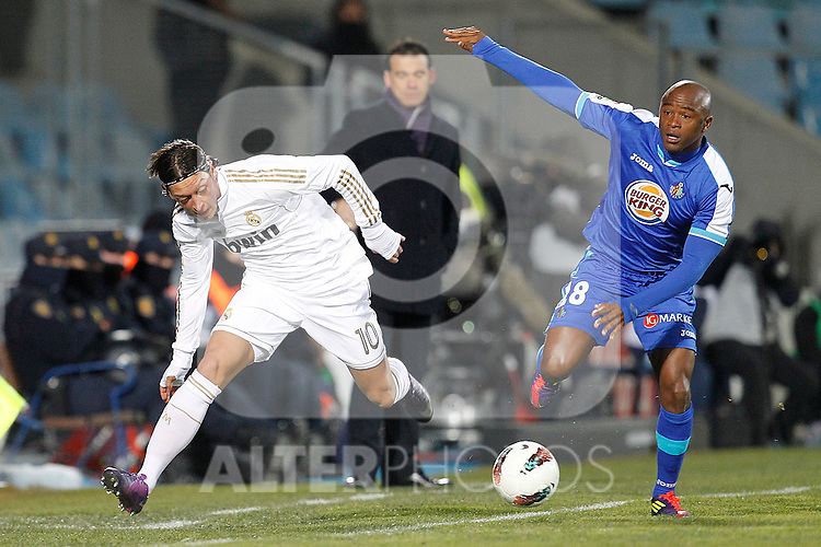 Getafe's Tshepo Masilela and Real Madrid's Mesut Ozil  during la Liga match on February 4th 2012. ..Photo: Cesar Cebolla / ALFAQUI