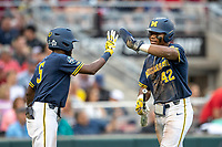 Michigan Wolverines designated hitter Jordan Nwogu (42) is greeted by teammate Christian Bullock (5) after scoring during Game 6 of the NCAA College World Series against the Florida State Seminoles on June 17, 2019 at TD Ameritrade Park in Omaha, Nebraska. Michigan defeated Florida State 2-0. (Andrew Woolley/Four Seam Images)