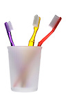 three toothbrushes in frosted glass on shadowless white background