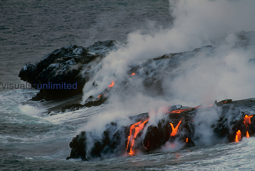 Hot lava flow from Kilauea volcano entering the Pacific Ocean and creating steam, Hawaii, USA.