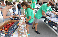 NWA Democrat-Gazette/DAVID GOTTSCHALK Kim Sparks (center), with the Georgia Peach Connection, helps Jaclyn Johnson Friday, July 5, 2019, select a box of peaches at their pop up stand on College Avenue in Fayetteville. The Georgia Peach Connection is on a four week tour selling free stone peaches from Pearson Farm in Fort Valley, Georgia. The Connection will be in Bentonville, Rogers and Fort Smith today.