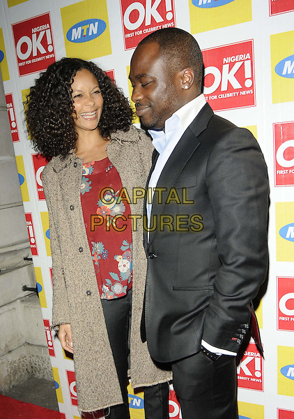 Thandie Newton & guest.The OK! Magazine Nigeria edition launch party, Nigerian Embassy, Northumberland Avenue, London, England..March 19th, 2012.half length beige brown coat red floral print top black suit profile.CAP/CAN.©Can Nguyen/Capital Pictures.