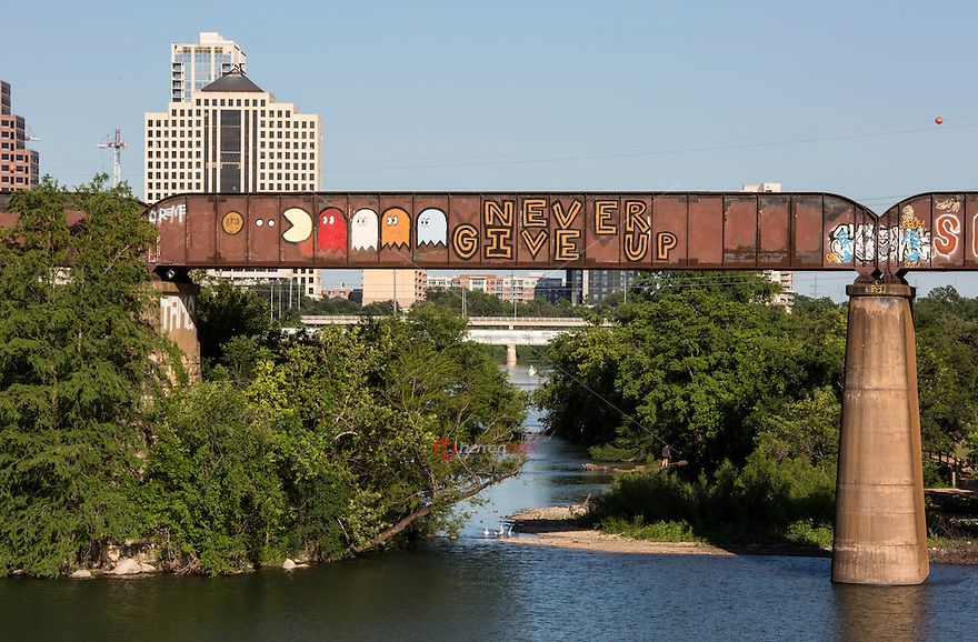 ìNever Give Upî is a famous beloved public art graffiti painting by artist SKO on Austinís Railroad Graffiti Bridge extending over Lady Bird Lake in downtown Austin, Texas - Stock image.