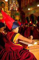 Buddhist monks chanting Losar prayers inside a monastery, Sikkim, India