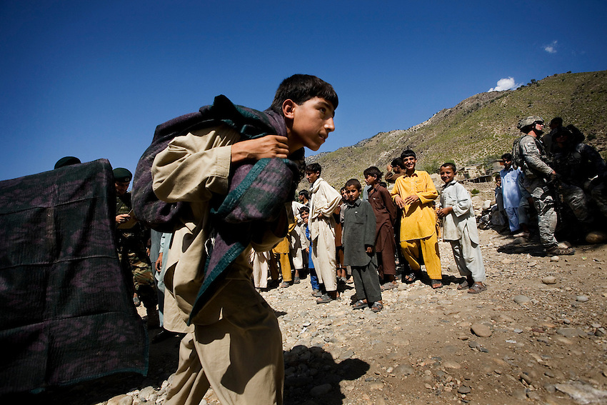 A boy walks away with a blanket full of humanitarian aid that was handed out by the Afghan National Army under the supervision of the US Marines and US Army in the village of Tarale in the Pesh Valley, Kunar Province, Afghanistan, Monday, Sept 28, 2009. The humanitarian aid was handed out with the cooperation of village elders who designated the poorest families in the village to give the majority of the aid to. Items given included palm oil, tea, radios, blankets, children's clothing, flour and rice.
