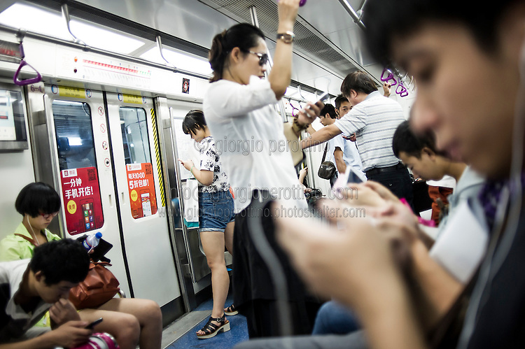 Chinese people use their smartphones in a train of the subway metro line in Beijing, China, August 15, 2014.<br /> <br /> Smartphones are an essential tool of Chinese ordinary life. Everywhere in China, people use them to take pictures to share online, to talk and chat, to play videogames, to get access to the mainstream information, to get connected one each other. In the country where the main global social media are forbidden - Facebook, Twitter and Youtube are not available  -, local social networks such as WeChat have a wide spread all over the citizens. The effect is an ordinary and apparently compulsive way to get easy access to digital technology and modern way of communication. <br /> A life through the display. Yes, We Chat.<br /> <br /> © Giorgio Perottino