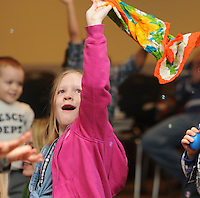 NWA Media/ J.T. Wampler - Anna Mason of Fayetteville, waves a scarf while listening to a live performance Saturday Dec. 27, 2014 at the Fayetteville Public Library. Jeremy Babcock of Chicago and the band Dreamtree Shakers performed a free show for children.