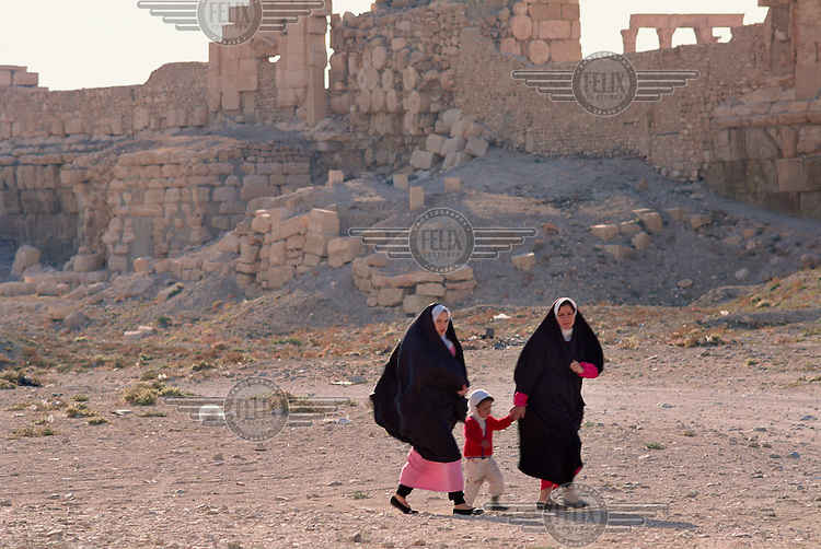 Two women walking with a child past the Roman-era ruins of Palmyra, in the Syrian desert.