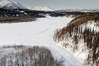 A team runs on the trail along the Happy River, at the confluence of the Skwentna River between the Finger Lake and Rainy Pass checkpoint during Iditarod 2016.  Alaska.  March 07, 2016.  <br /> <br /> Photo by Jeff Schultz (C) 2016 ALL RIGHTS RESERVED