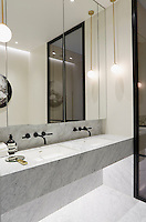 The spacious en suite bathroom is cool and stylish in grey marble with double set-in hand basins with Dornbracht taps.
