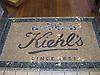 Custom mosaic retail signs - Kiehl's entry way in Thassos, Travertine Noce, Verde Luna, Verde Alpi, Nero Marquina polished
