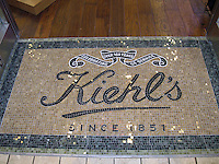 Custom mosaic retail signs - Kiehl's entry way in Thassos, Travertine Noce, Verde Luna, Verde Alpi, Nero Marquina polished