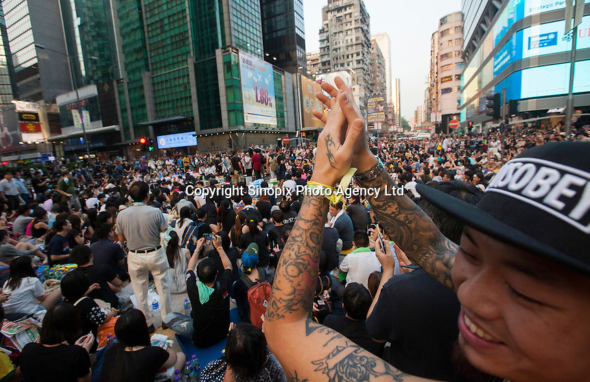 A pro-democracy protestor claps in Mong Kok, on the second day of the mass civil disobedience campaign Occupy Hong Kong, Mong Kok, Kowloon, Hong Kong, China, 30 September 2014. The movement is also being dubbed the 'umbrella revolution' after the versatile umbrellas used to shield protesters from rain, sun - and police pepper spray.