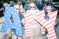"Supporters of Democratic presidential candidate and Minnesota senator Amy Klobuchar carry letters spelling ""AMY"" decorated like an American flag as they march in the 4th of July parade in Amherst, New Hampshire, on Thu., July 4, 2019."