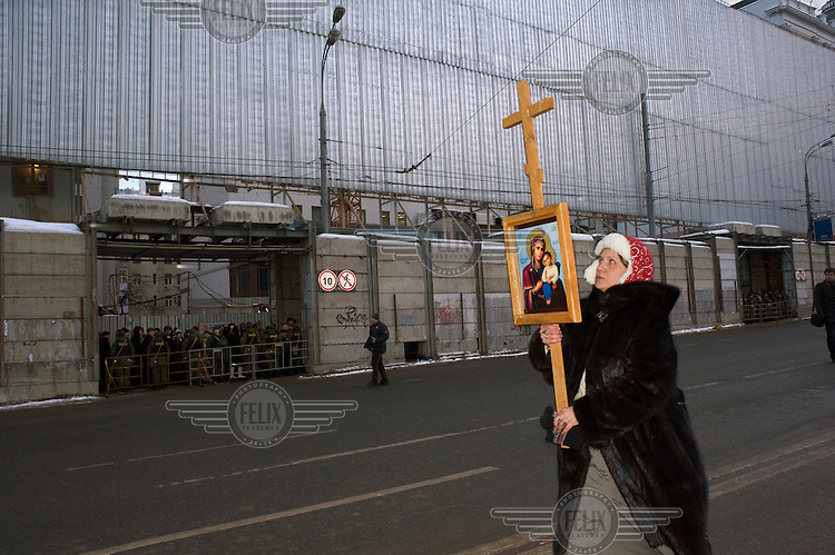 A woman carries a cross with an icon showing the Virgin Mary and Jesus across Pushkin Square while protesters and riot police look on in the distance. Tens of thousands of people came out onto the streets of Moscow and other Russian cities following the announcement of the results of the presidential election which saw Prime Minister Vladimir Putin elected to the presidency with 64 % of the vote. ..