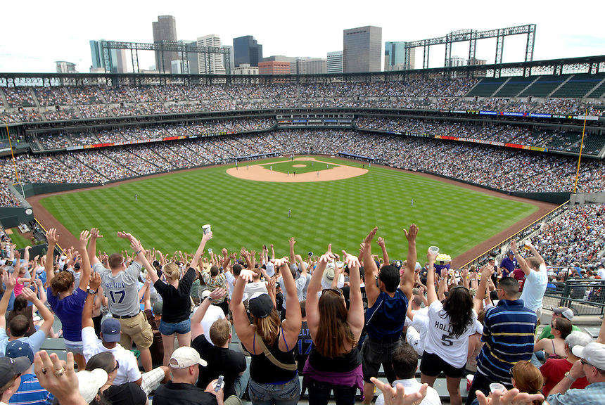 """25 May 2008: Baseball fans raise their arms as """"the wave"""" makes its way around Coors Field, during a game between the Colorado Rockies and the New York Mets. The Rockies defeated the Mets 4-1 at Coors Field in Denver, Colorado."""