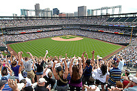 "25 May 2008: Baseball fans raise their arms as ""the wave"" makes its way around Coors Field, during a game between the Colorado Rockies and the New York Mets. The Rockies defeated the Mets 4-1 at Coors Field in Denver, Colorado."