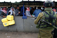 Palestinians stand on line at the Hawara checkpoint in Nablus, West Bank, November 05, 2006, waiting for Israeli soldiers to check their ID cards. The Hawara checkpoint on the southern entrance of Nablus controls the movement of Palestinians between Nablus and the Southern part of the West Bank. The checkpoint, run by IDF paratroopers, doesn't limit with Israel. Photo by Quique Kierszenbaum