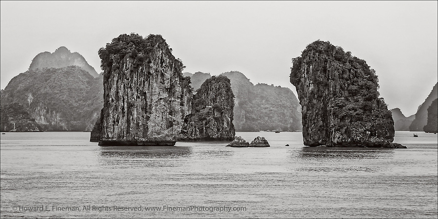 Sea Stacks, Ha Long Bay, Vietnam. To get a sense of scale, look at the barely visible boat in the right background.  A 4-foot long banner of this image is part of Newton's FenceART, moving every  2-3 months to a new bridge location in Newton.