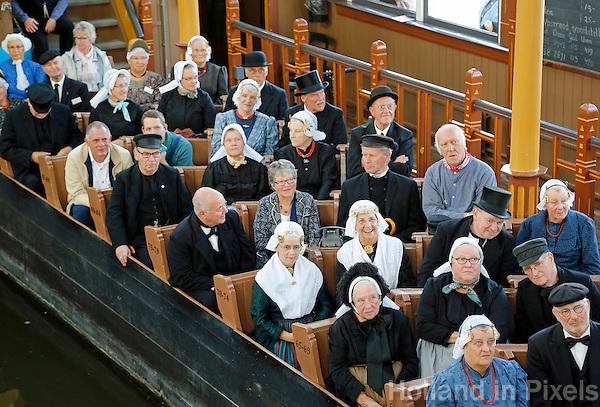 Nederland Broek op Langedijk 2015 . Nationale Folkloredag, met veel mensen in Nederlandse  klederdracht, bij Museum de BroekerVeiling. De Broekerveiling is de oudste doorvaarveiling ter wereld. Mensen in klederdracht zitten in de Afmijnzaal