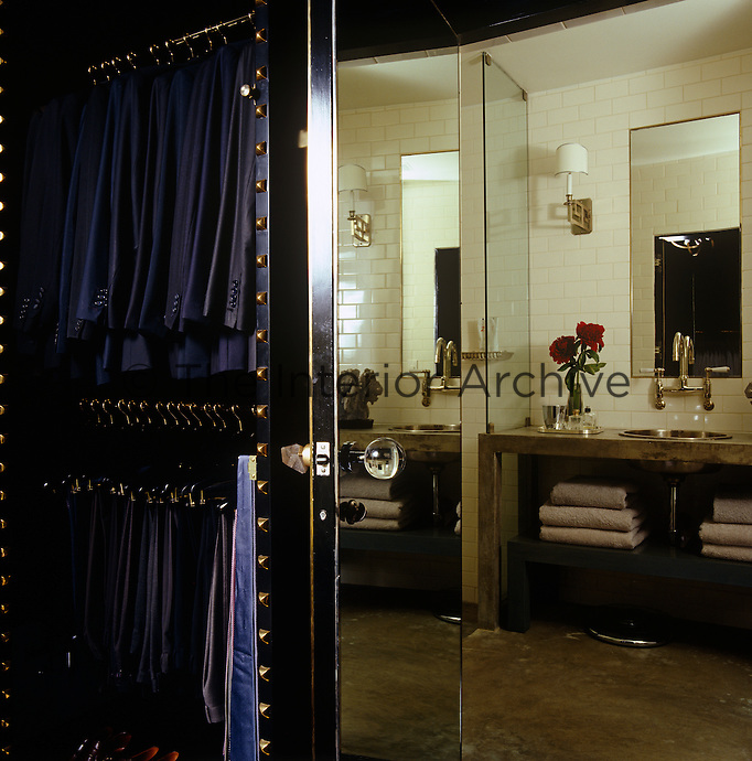 The dressing room opens into the master bathroom via a mirrored glass door